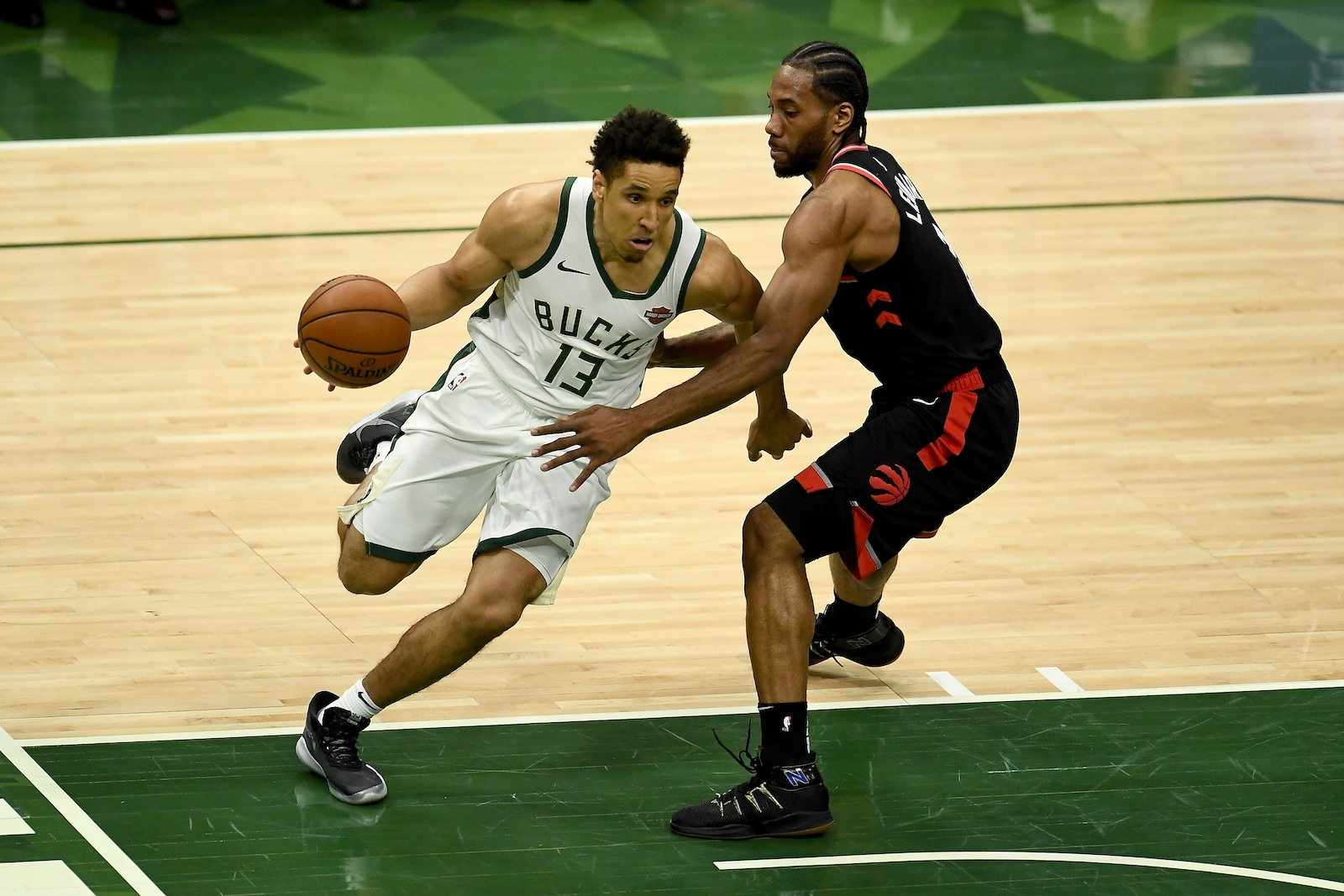 Malcolm Brogdon #13 of the Milwaukee Bucks dribbles the ball while being guarded by Kawhi Leonard #2 of the Toronto Raptors