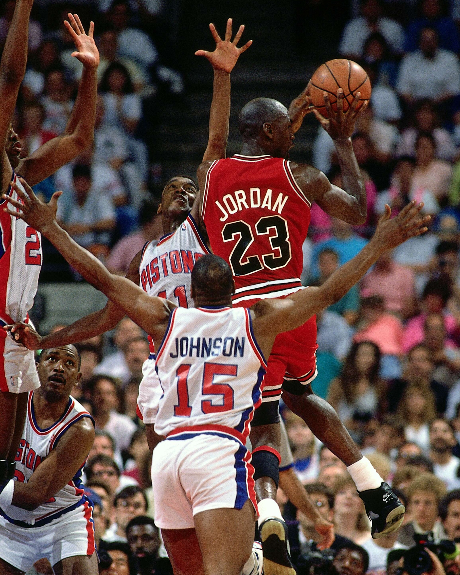 The Pistons defense collapses on a driving Jordan.