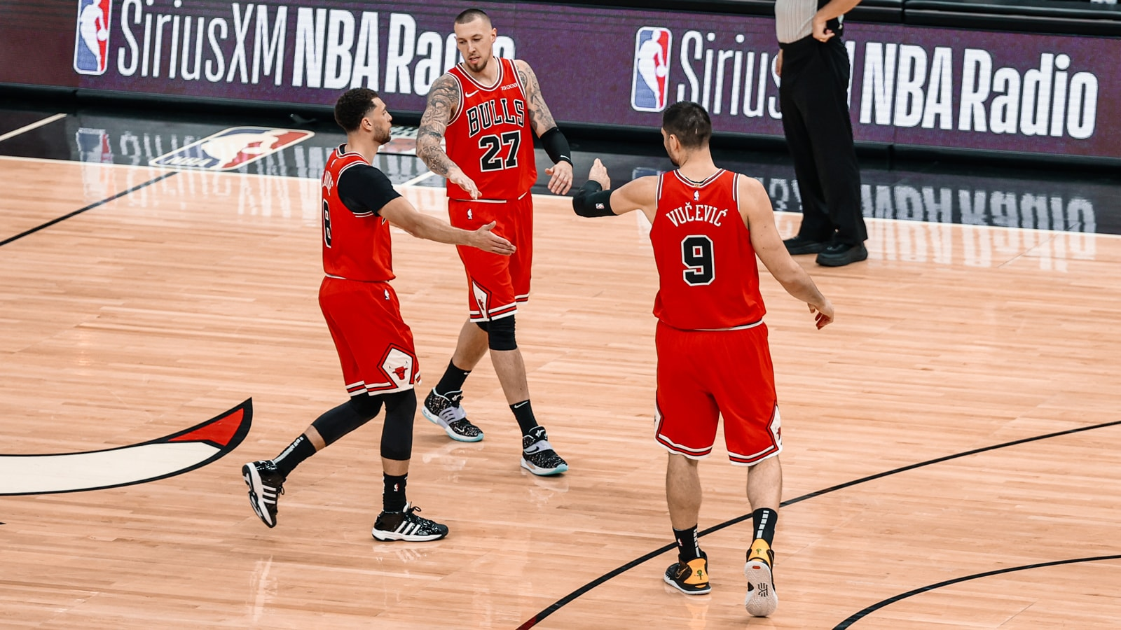 Zach LaVine is greeted by Daniel Theis and Nikola Vucevic on the United Center floor