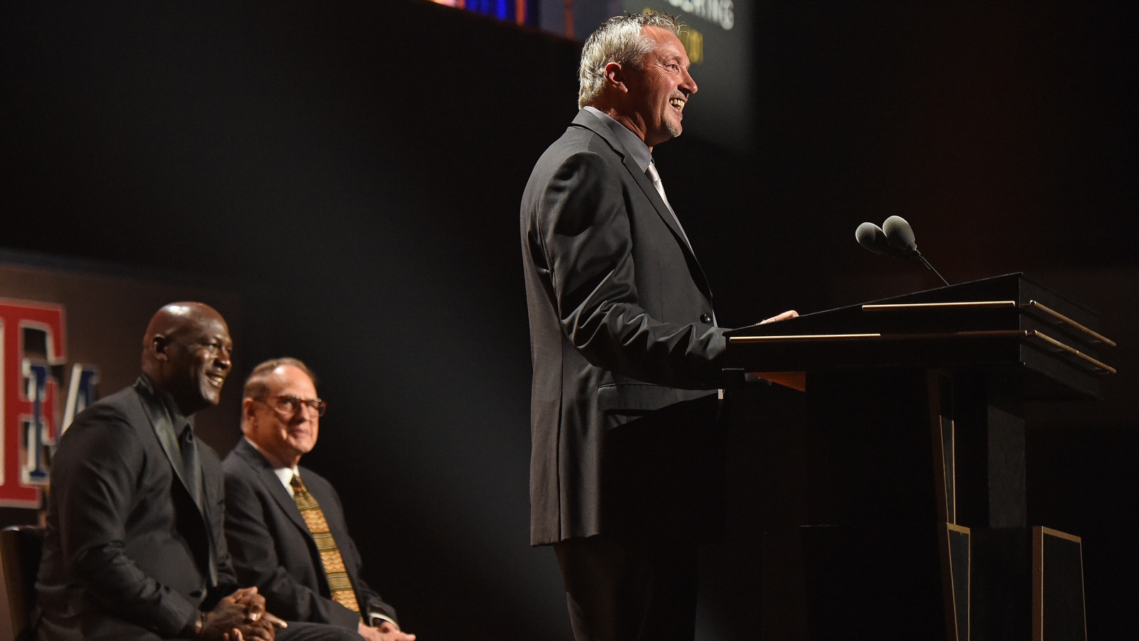 Toni Kukoc speaks during his Hall of Fame induction ceremony as his presenters Michael Jordan and Jerry Reinsdorf looks on.