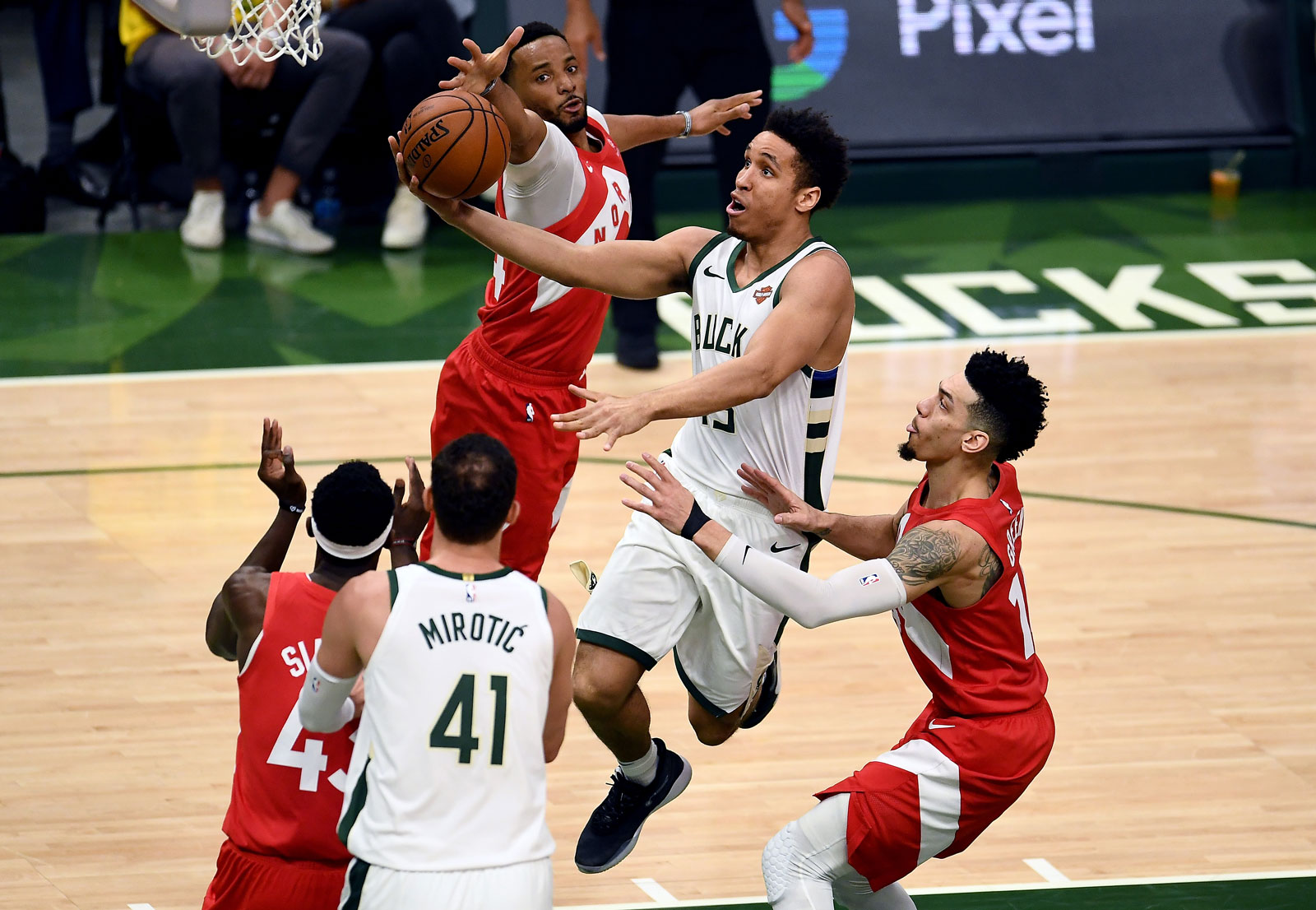 Malcolm Brogdon #13 of the Milwaukee Bucks attempts a shot while being guarded by Pascal Siakam #43 and Danny Green #14 of the Toronto Raptors in the second quarter during Game Five of the Eastern Conference Finals of the 2019 NBA Playoffs at the Fiserv Forum on May 23, 2019 in Milwaukee, Wisconsin.