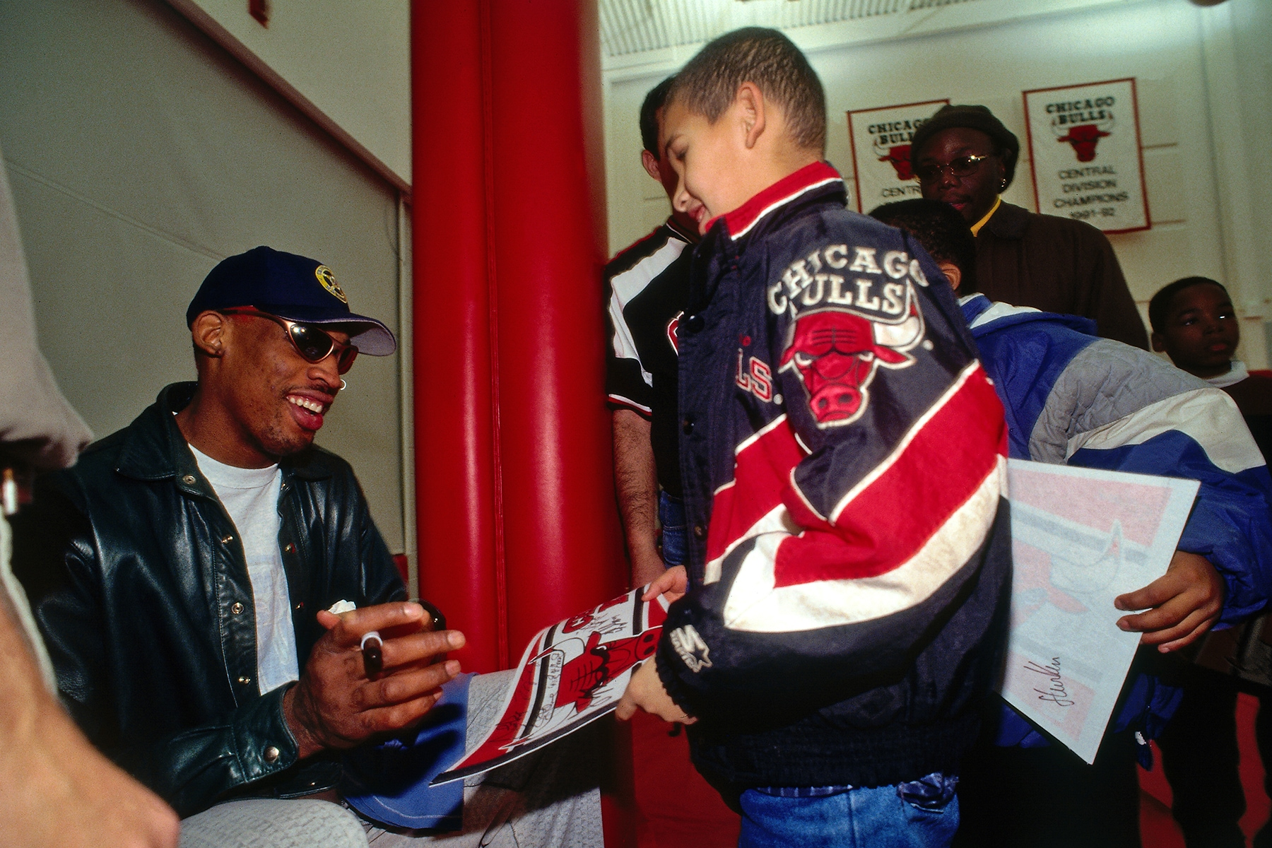 Dennis Rodman signs an autograph for a young fan
