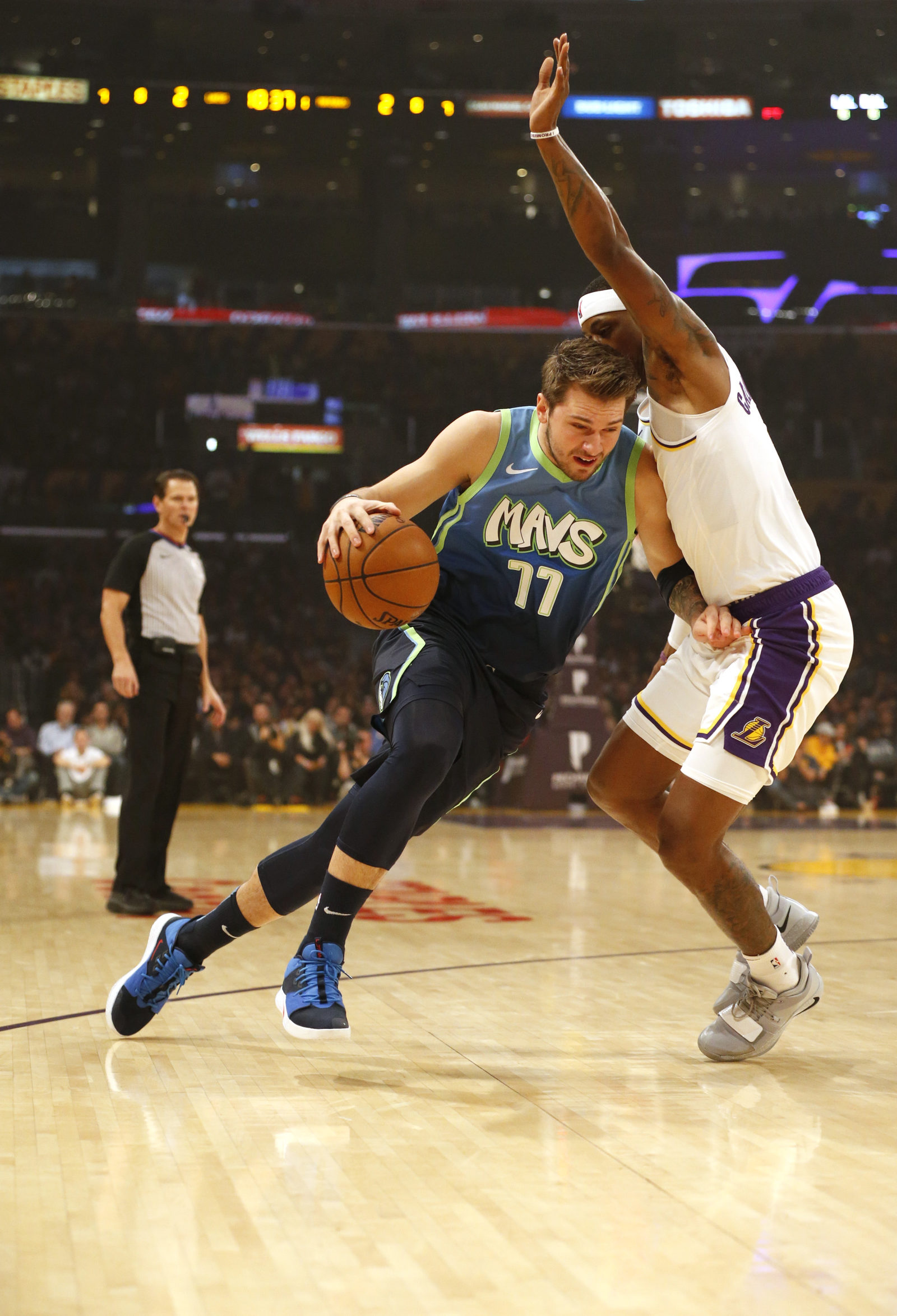 Luka Doncic #77 of the Dallas Mavericks drives around Kentavious Caldwell-Pope #1 of the Los Angeles Lakers during the first half at Staples Center on December 01, 2019 in Los Angeles, California.