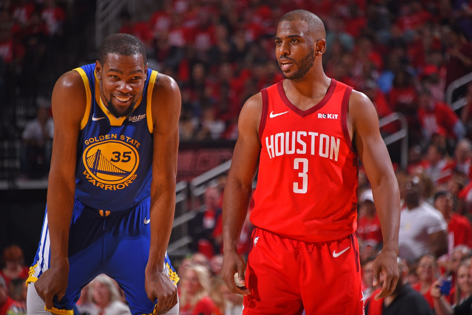 Kevin Durant #35 of the Golden State Warriors and Chris Paul #3 of the Houston Rockets smile during Game Four of the Western Conference Semifinals of the 2019 NBA Playoffs on May 6, 2019 at the Toyota Center in Houston, Texas.