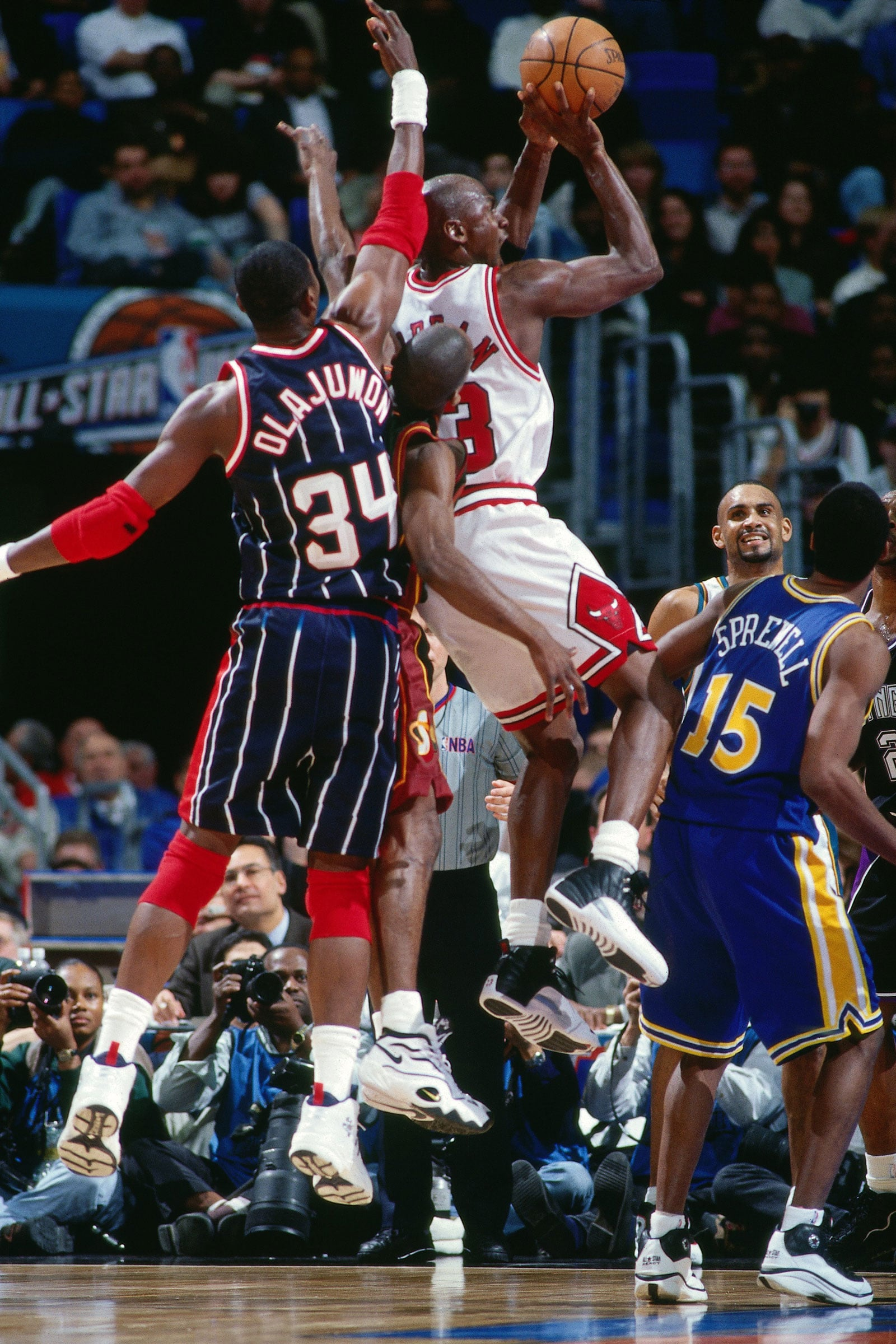 Michael Jordan #23 of the Eastern Conference shoots against Hakeem Olajuwon #34 of the Western Conference during the 1997 All-Star Game on February 9, 1997 at Gund Arena in Cleveland, Ohio
