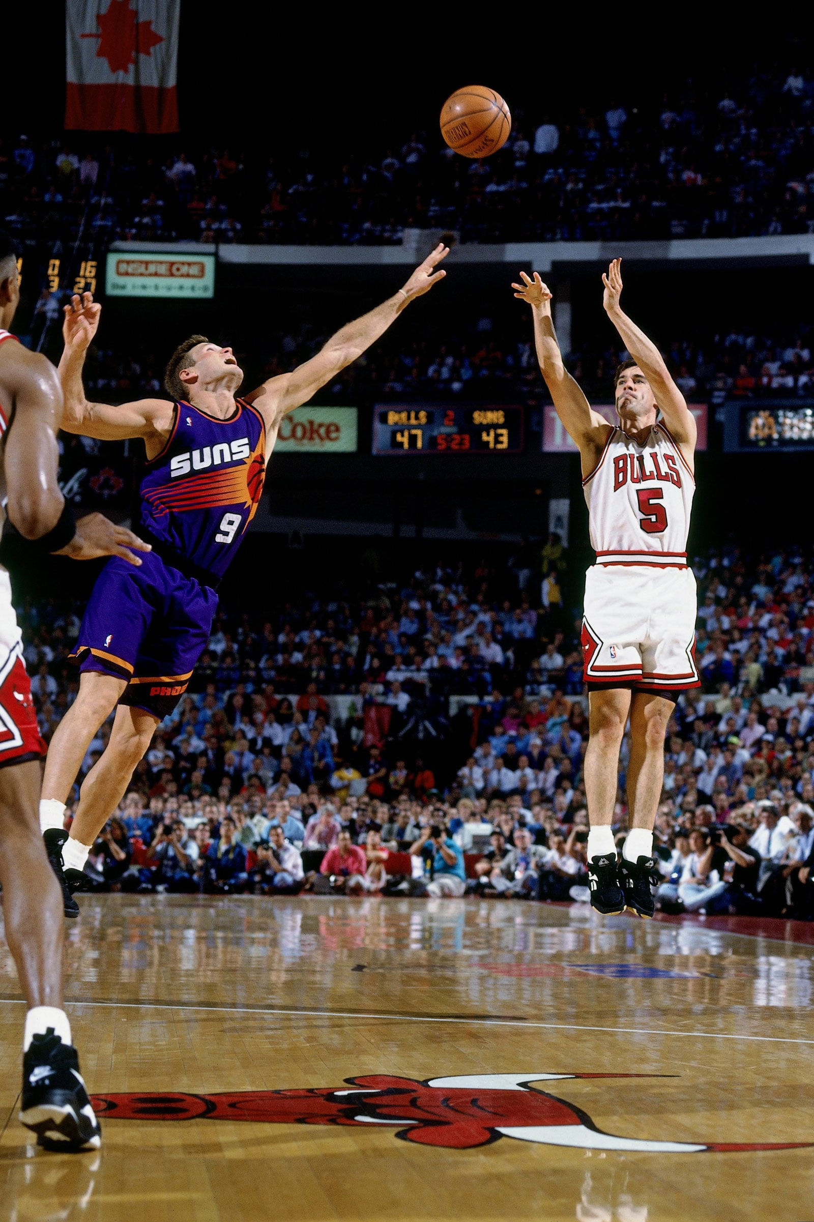 John Paxson #5 of the Chicago Bulls attempts a shot against Dan Majerle #9 of the Phoenix Suns in Game Four of the 1993 NBA Finals on June 16, 1993 at the Chicago Stadium in Chicago, Illinois. The Bulls won 111-105