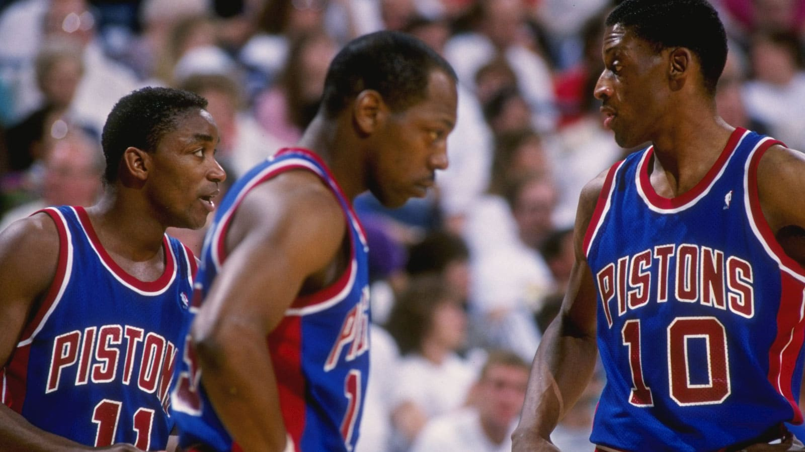 Guard Isiah Thomas, left, forward Dennis Rodman, right, and forward Vinnie Johnson of the Detroit Pistons talk to each other during a game.