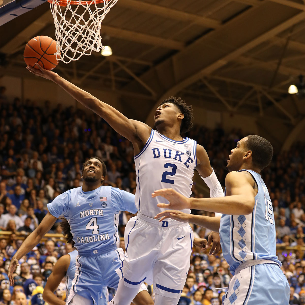 Cam Reddish #2 of the Duke Blue Devils drives to the basket against teammates Brandon Robinson #4 and Garrison Brooks #15 of the North Carolina Tar Heels during their game at Cameron Indoor Stadium on February 20, 2019 in Durham, North Carolina.
