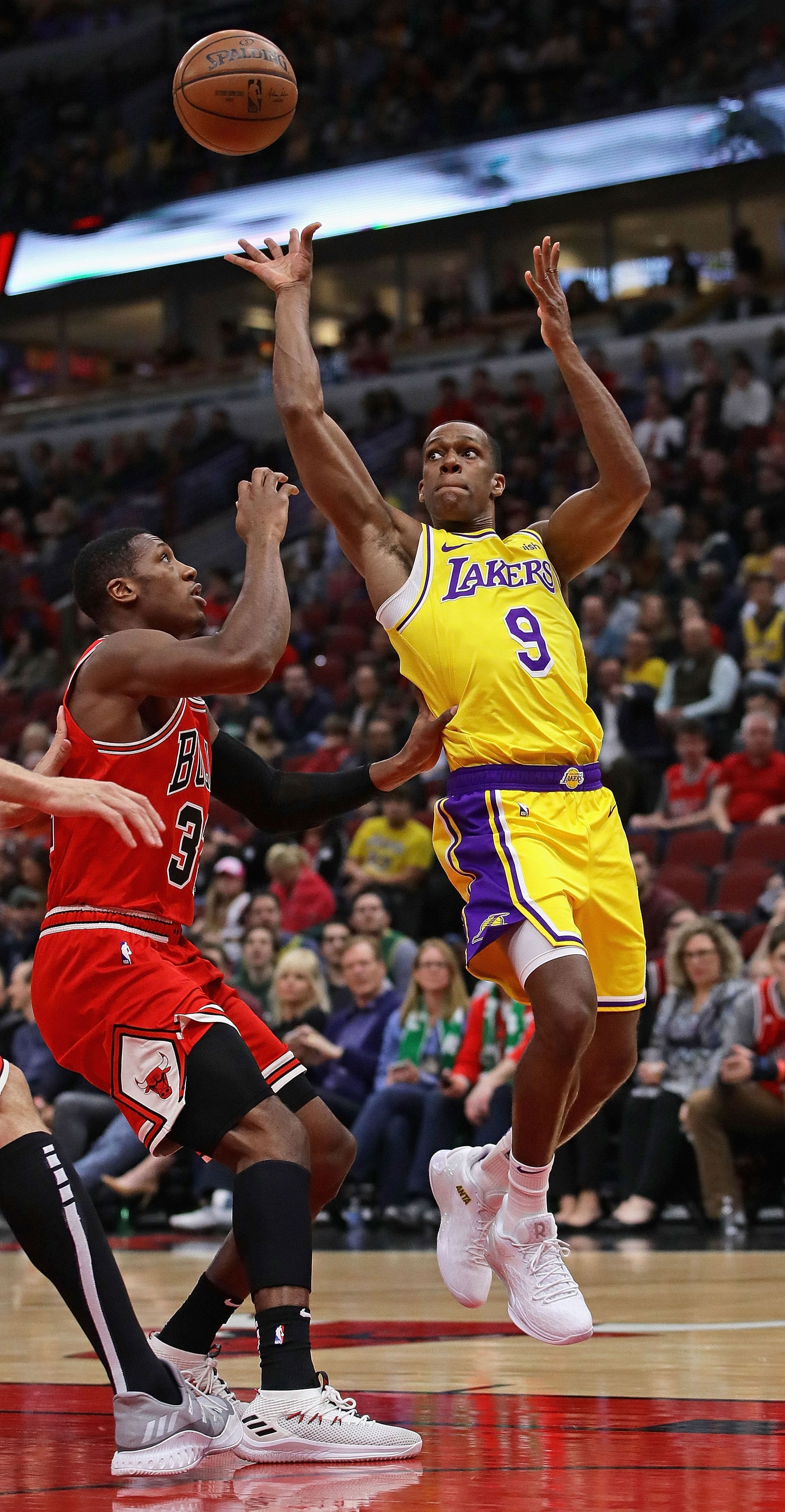 Rajon Rondo #9 of the Los Angeles Lakers lofts a pass over Kris Dunn #32 of the Chicago Bulls at the United Center on March 12, 2019 in Chicago, Illinois.