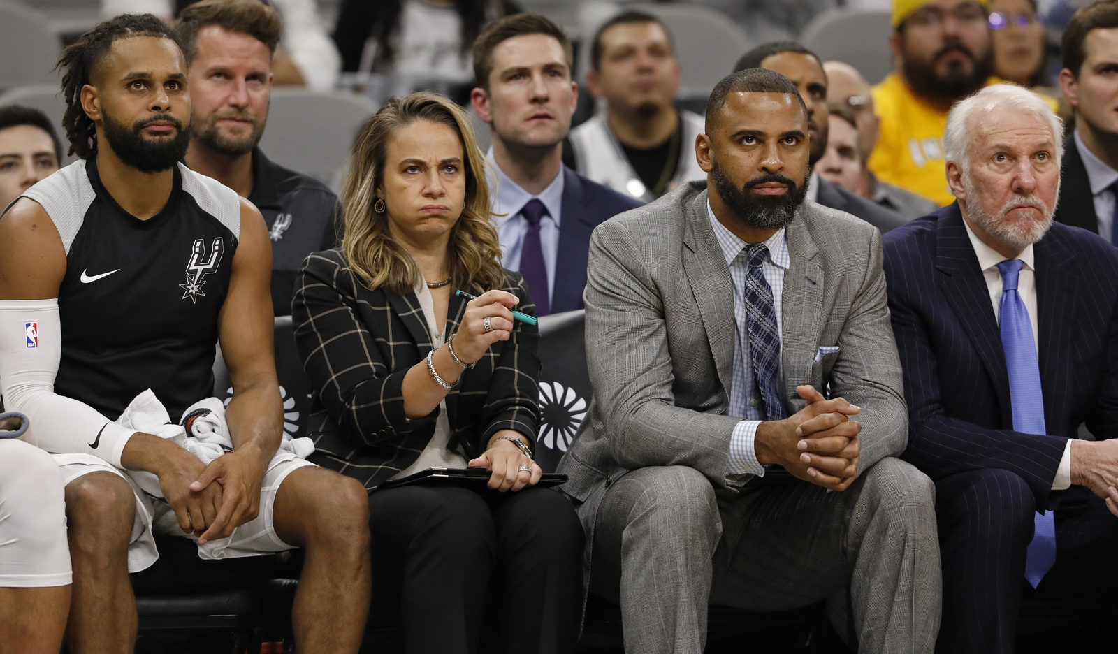 Patty Mills #8 of the San Antonio Spurs, assistant coaches Becky Hammon, Ime Udoka, and head coach Gregg Popovich watch action against the Indiana Pacers from the bench during an NBA game on October 24, 2018 at the AT&T Center in San Antonio, Texas.