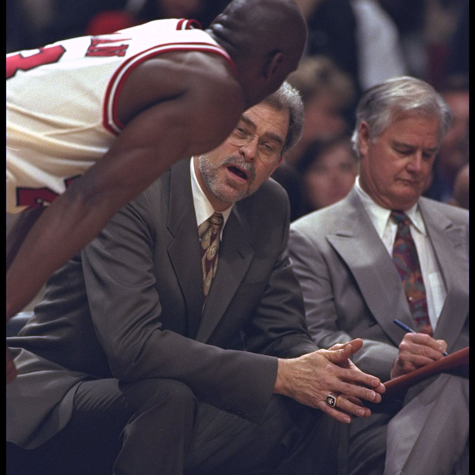 Head coach Phil Jackson of the Chicago Bulls talks with Michael Jordan and Tex Winter during the first round of the NBA Playoffs against the Washington Bullets at United Center in Chicago, Illinois