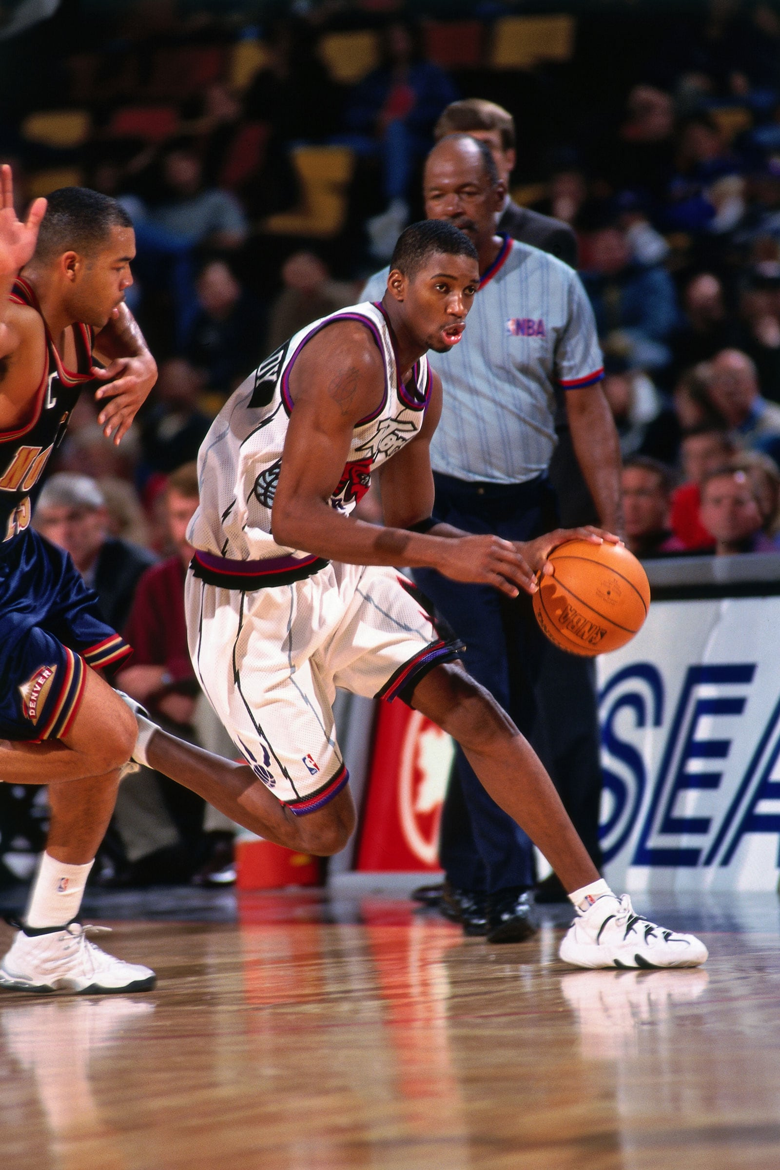 Tracy McGrady #1 of the Toronto Raptors dribbles against the Denver Nuggets on March 19, 1998 at the Skydome in Toronto, Canada.