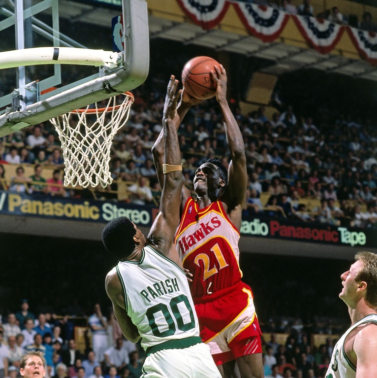 Dominique Wilkins #21 of the Atlanta Hawks dunks against Robert Parish #00 of the Boston Celtics during a game played in 1988 at the Boston Garden in Boston, Massachusetts.