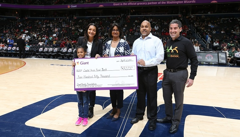 Capital Area Food Bank is presented a check at mid-court in the Capital One Arena